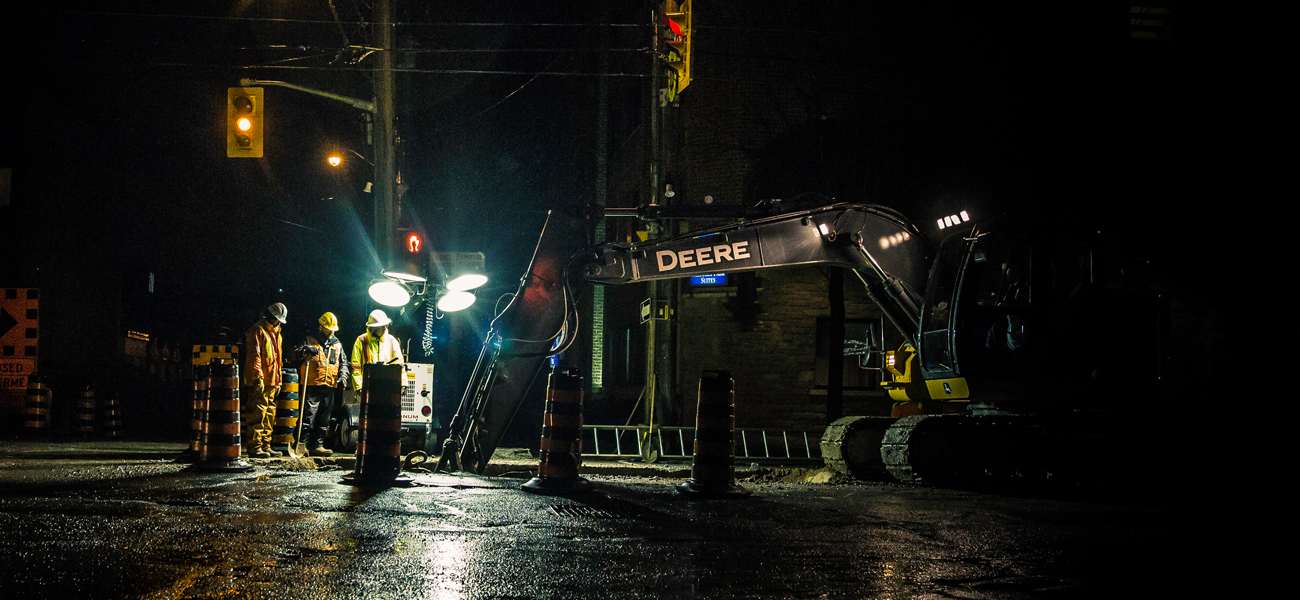 Construction workers repairing road at night