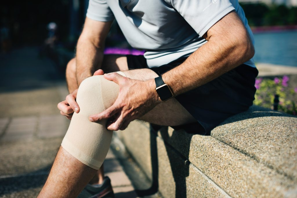 man clutching sore knee