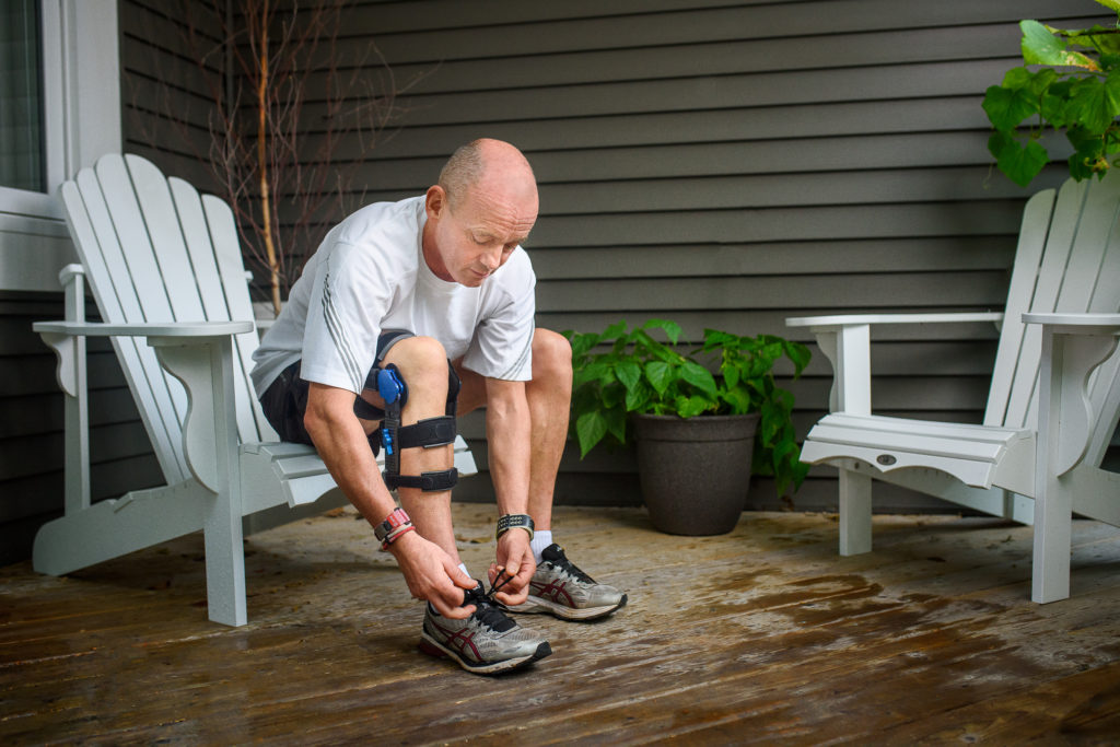 Man with Knee arthritis brace tying shoe
