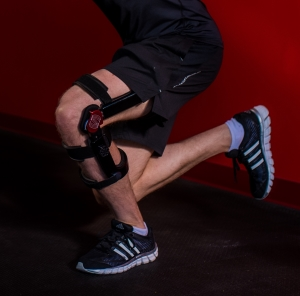 Person performing a one legged squat with a knee extension assist brace.